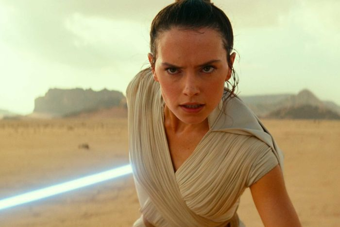 A woman wearing a white robe and carrying a lightsaber stands in a desert.