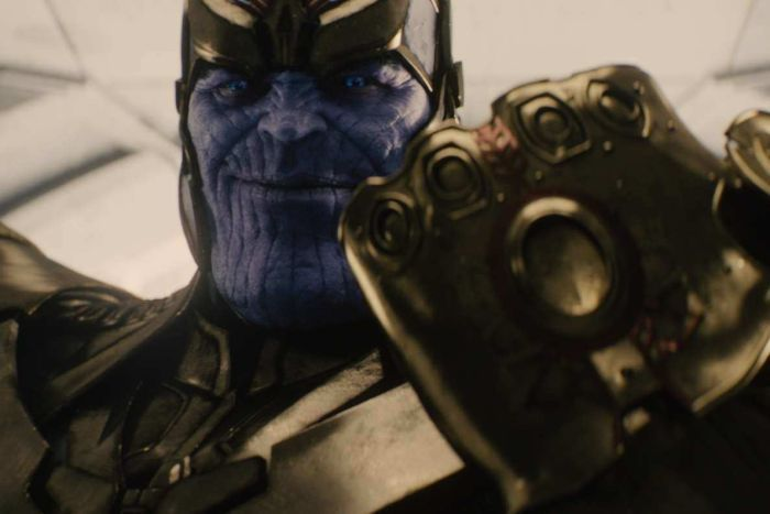 Thanos, a purple titan in gold armour, holds the golden Infinity Gauntlet.