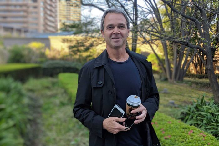 Paul Morgan stands in a coat with a coffee