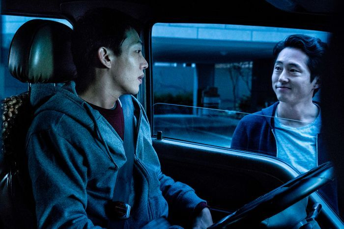 Colour still of Yoo Ah-in sitting in car and Steven Yeun standing outside car window in 2018 film Burning.