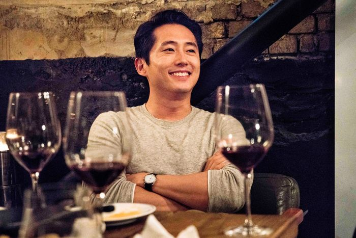 Colour still of Steven Yeun smiling in front of table of wine glasses 2018 film Burning.