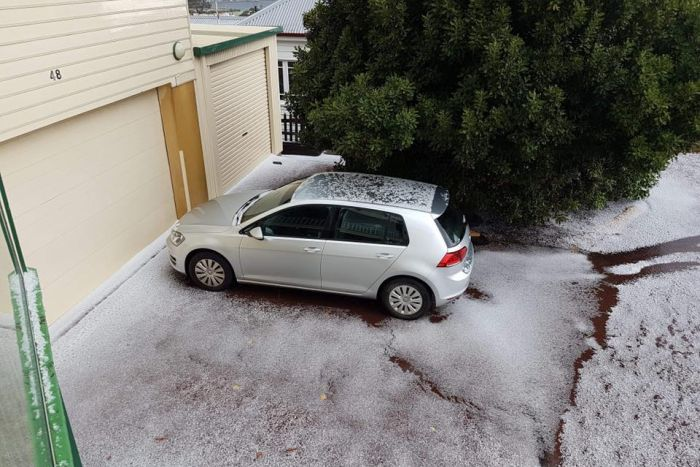 A car sits in front of an iced garage with sleet on the ground, next to a green tree.