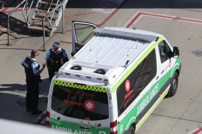 Police talk next to an ambulance parked on an airport tarmac.