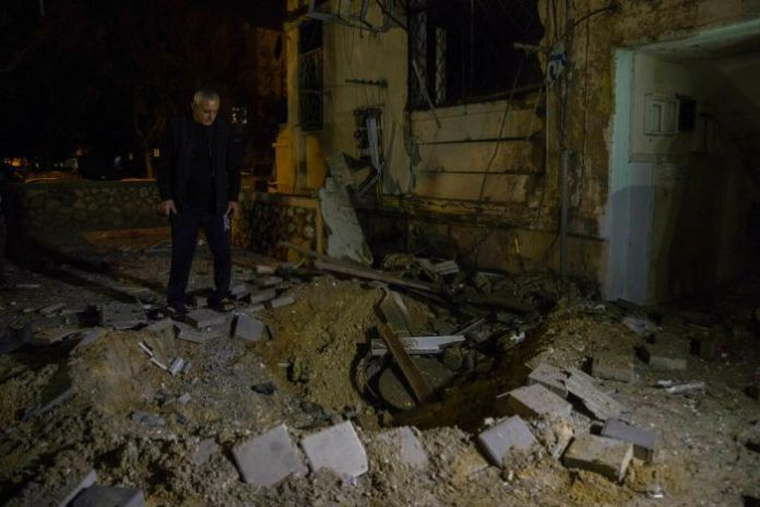 A man looks at a small crater in the ground next to a darkened and damaged building.
