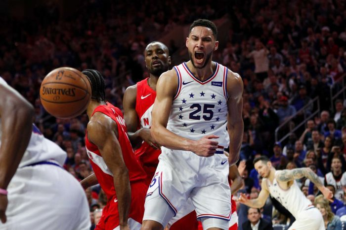Ben Simmons screams and clenches his fist while wearing a white singlet with stars on it