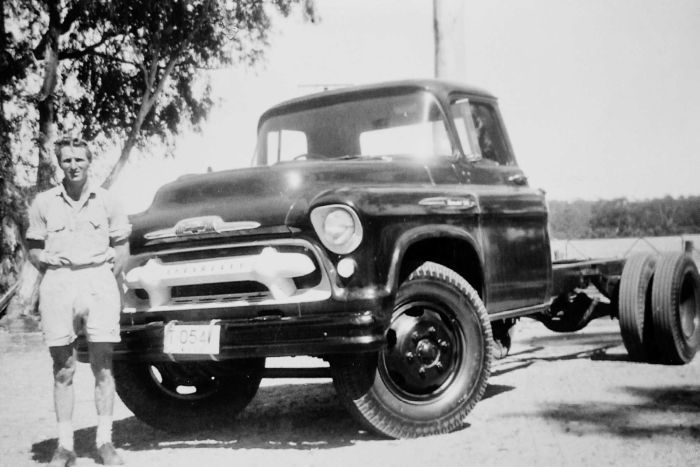 An old black and white photo of Norman Simon standing beside his Chev truck.
