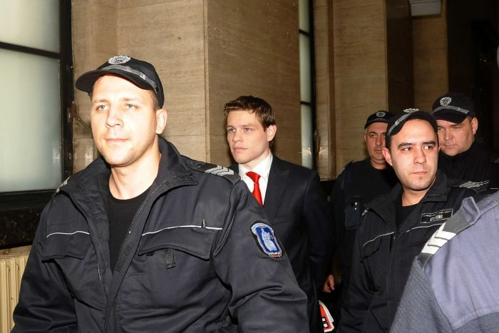 A man wearing a suit and red tie is surrounded by police officers