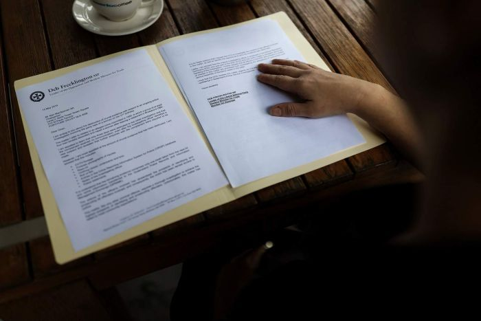 """Alleged gang rape victim """"Eve"""" looking at a letter sent to Alan MacSporan from Deb Frecklington, May 2019."""