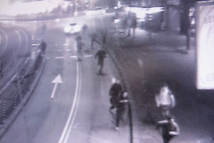 A slightly fuzzy still from CCTV showing a group of people running down a street