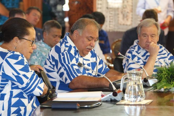 Three people wearing matching blue and white shirts sit at a conferences table speaking into microphones.