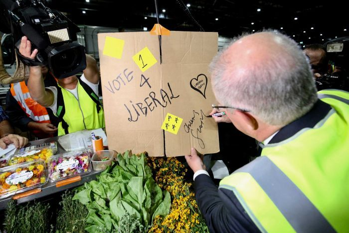 """Scott Morrison signs """"cheers ScoMo"""" on a cardboard sign with """"vote 4 Liberal"""""""