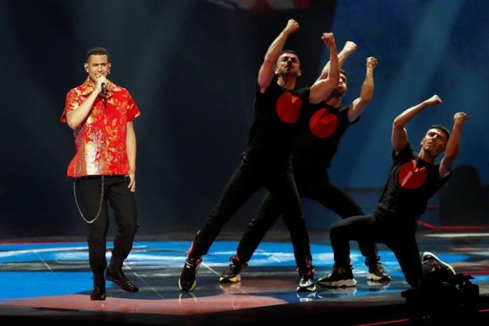 Mahmood, left, wears a red shirt as three dancers in black stand to his right. Mahmood is singing.