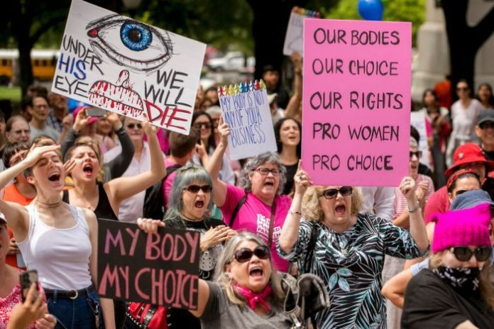 A group of women mostly screaming and waving banners in favor of the choice to protest the restrictive abortion laws.