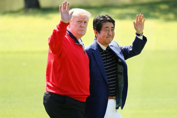 Mr Trump and Mr Abe wave to cameras as they walk on a golf course.