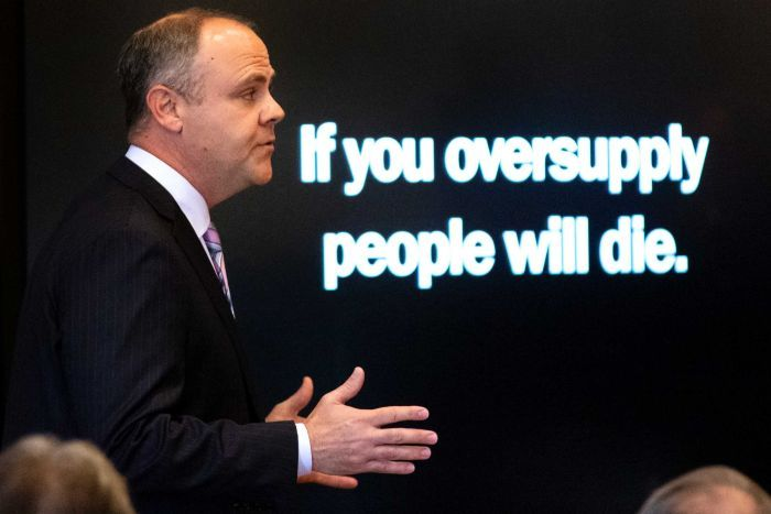 """State attorney Brad Beckworth speaks with a screen which reads, """"If you oversupply people will die"""", behind him."""