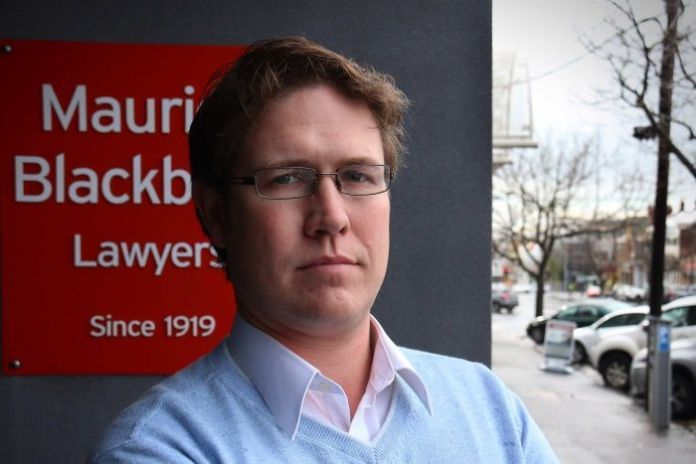 Sebastian Smith is in front of an office of Maurice Blackburn.