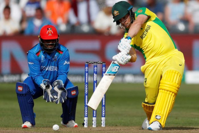 Aaron Finch drives hard through the covers while the wicketkeeper watches on.
