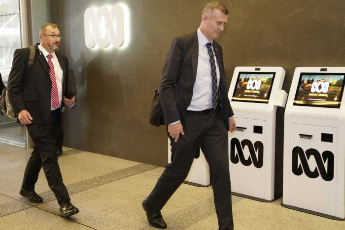 Two men in suits enter the ABC.