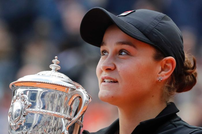 A tennis player stands with the trophy after winning the French Open women's singles final.