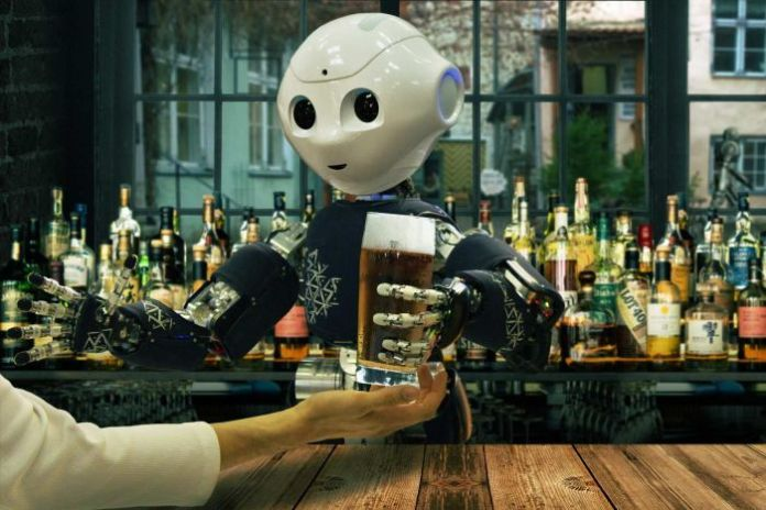 A robot serves a glass of beer from behind a well-stocked bar.