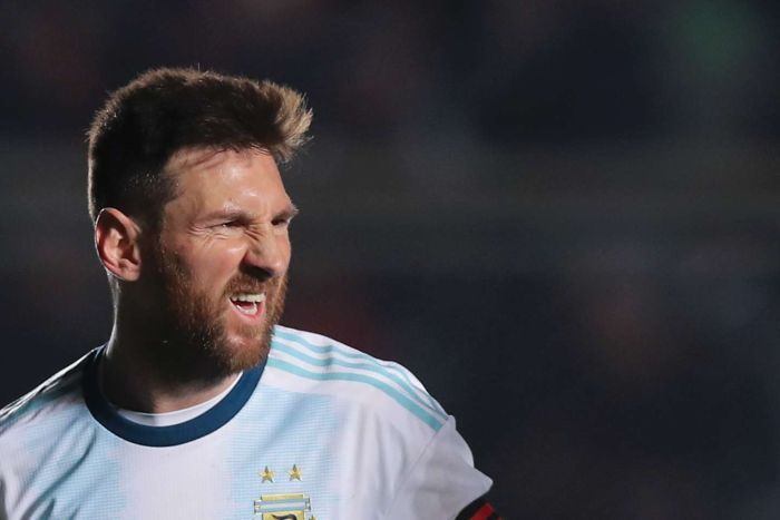 A head shot of Lionel Messi scrunching his face in celebration
