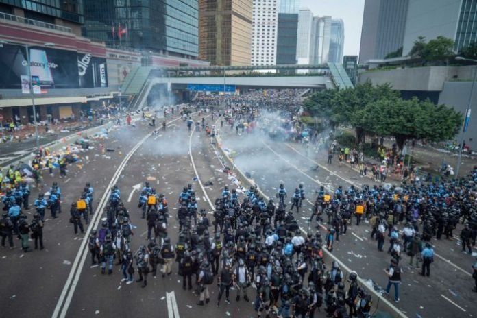 Riot police launch tear gas