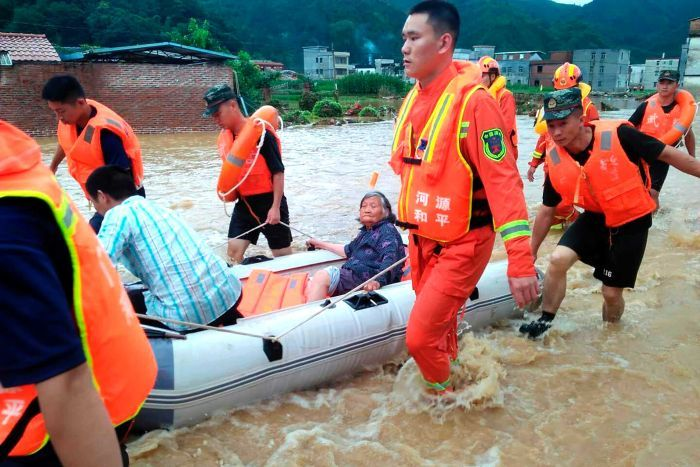 rescuers evacuate an elderly woman on a boat over a body of water
