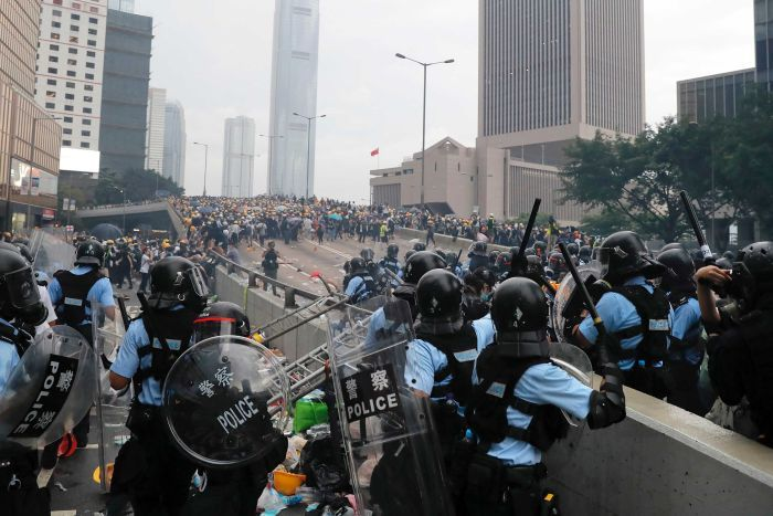 Looking down a raised expressway, Hong Kong police present a blockage to hundreds of protesters gathered further up the road.