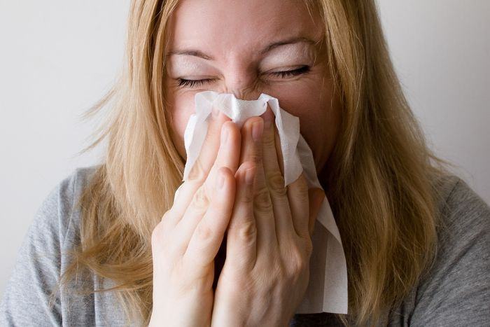 A woman blows her nose her tissue.