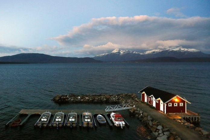 A common view of a small harbor and snow-capped mountains on the Bals-Fiord, north of the Artic Circle