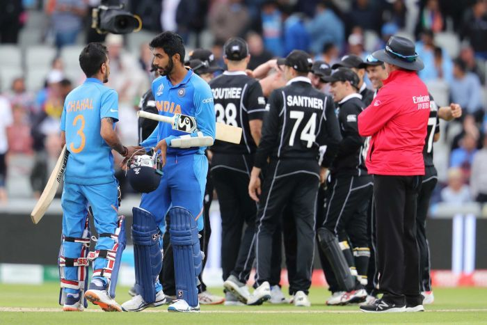 Yuzvendra Chahal and Jasprit Bumrah in the foreground with New Zealand celebrating in the background