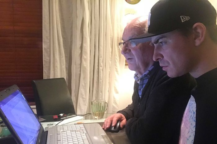 Two men looking at a computer screen searching for results.
