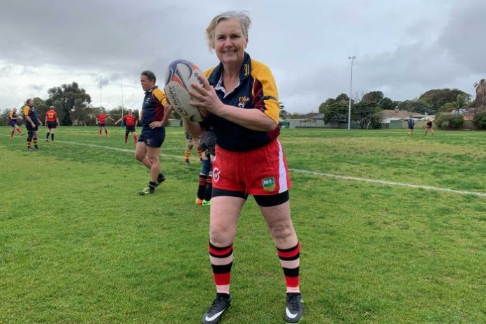 A senior female rugby player holds the ball