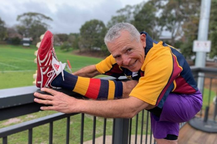 A senior rugby player stretches before his game