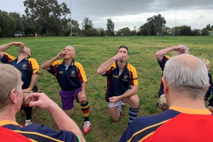 Senior rugby players kneel on the track to take a shot of the harbor