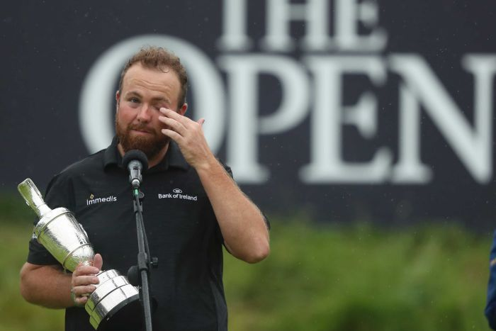 Shane Lowry, standing at a microphone, wipes at his eye with his left hand while holding a trophy with his right.