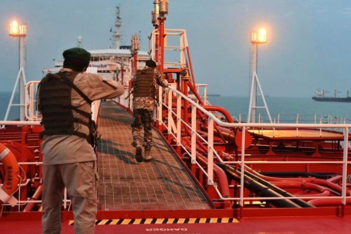Two armed members of the Iranian Revolutionary Guard travel a passage on a bright red ship.
