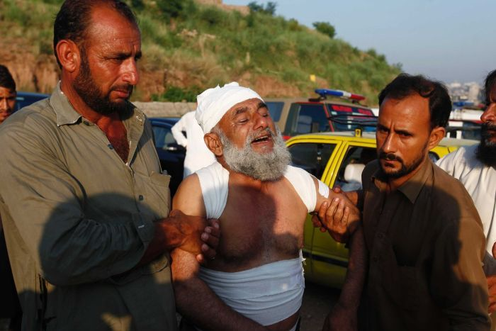 A man is being supported by two men on either side as he mourns/cries