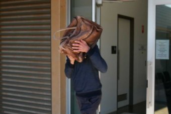 A man exits a court building with a bag covering his head and face.