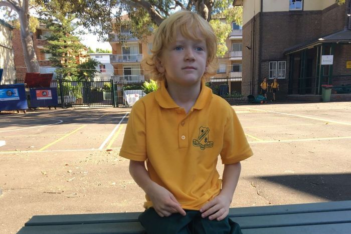 A boy with strawberry blond hair and a yellow school uniform sits in his school playground