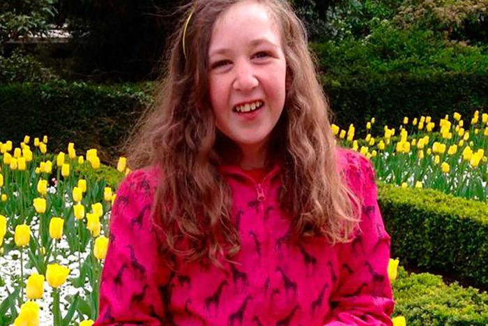 Nora Quoirin smiles as she wears a pink coat and purple tights. Her long hair flows over it as she stands in front of tulips.