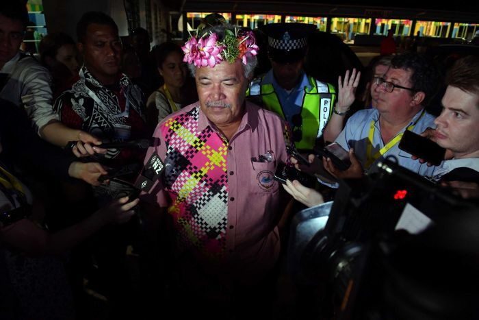 Tuvalu's Prime Minister Enele Sopoaga walks thorough a crowd of press with their microphones pointed at him