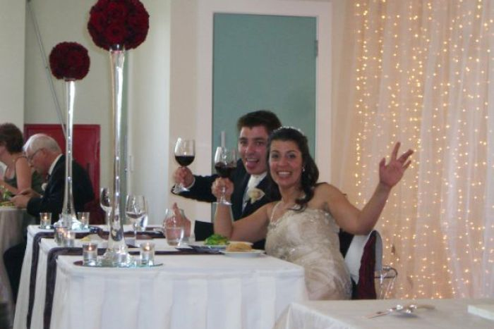 A married couple toasting the camera at their wedding reception.