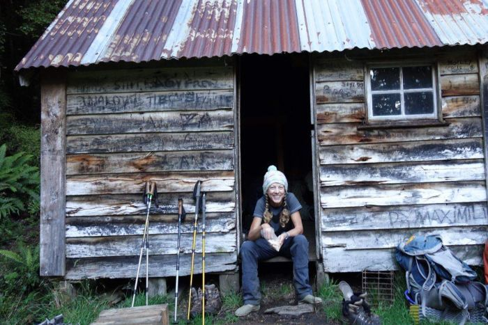 A smiling woman wearing beanie and casual clothes sits in the doorway of wooden hut with tin roof, next to a backpack.