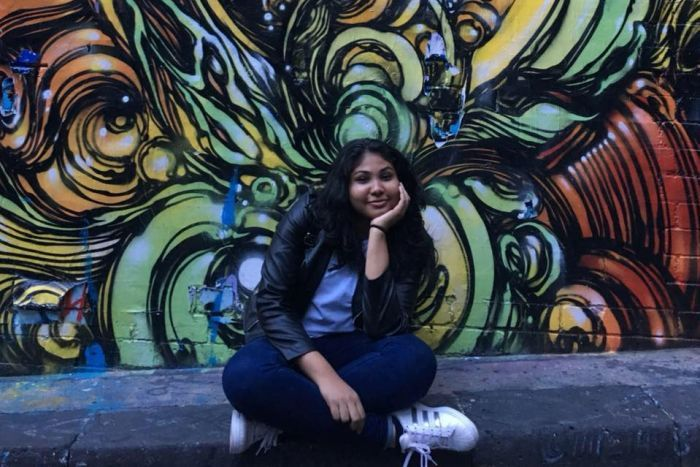Nisali Perera sits in front of a graffiti art wall smiling.