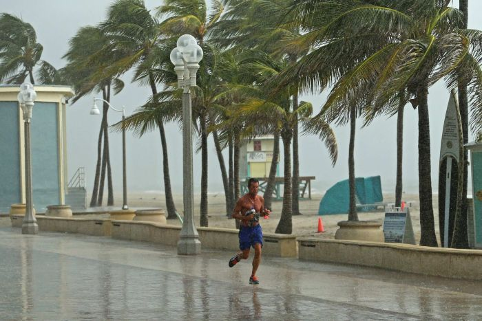 Man jogs alongside beach as huge winds and rain lashes him and area