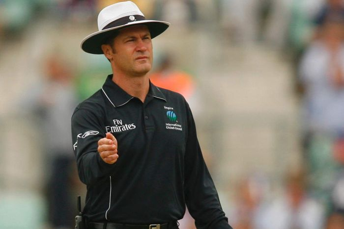 Simon Taufel is in all-black umpiring gear, holding a bowler's hat.