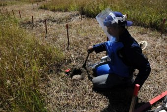 Looking down at a man in blue protective clothing and a full face shield as he works clearing a field of land mines.
