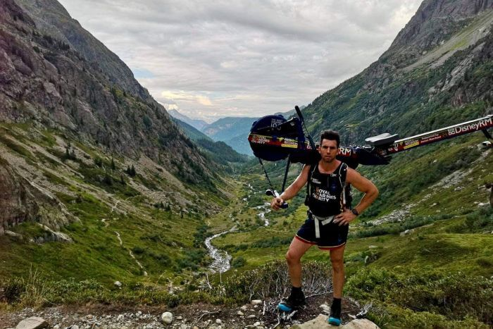Matthew Disney carries a rowing machine on his back on Mont Blanc.