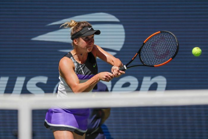 A tennis player hits a two-handed backhand return at the US Open.